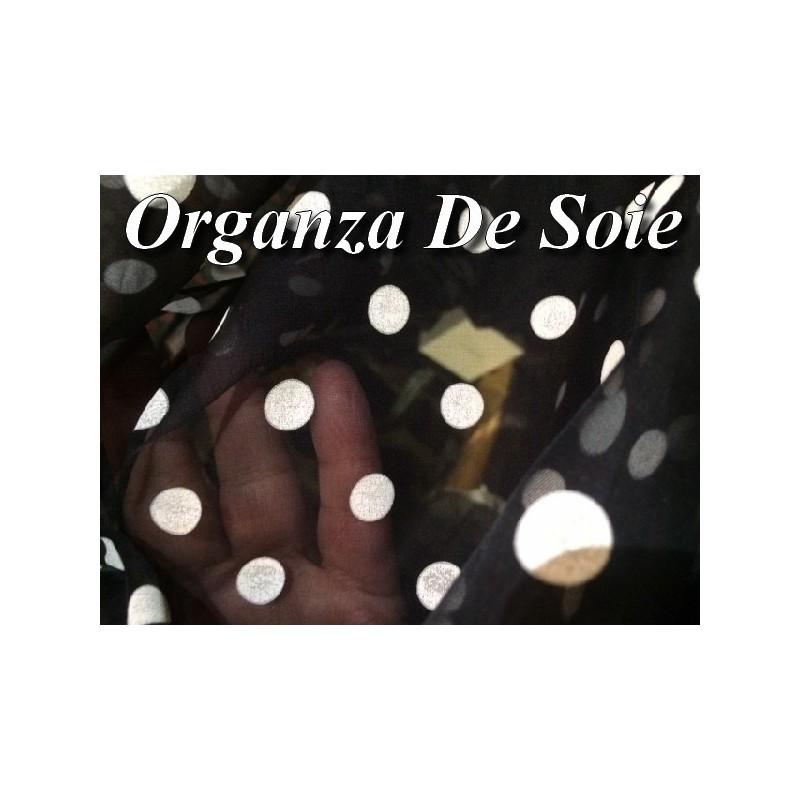 Tissu Organza en soie au mètre imprimé en motifs petit pois créme sur fond noir.