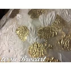 Tissu Brocart Couture En Motifs Fleurs FLoqués Couleur Ivoire Et Fleurs Doré Or Imprimés Pour Robes, Tailleurs Et Caftans.